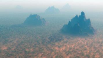 Aerial of dense forest with mountain peaks in the mist.