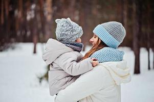 mãe feliz e bebê em uma caminhada aconchegante de inverno na floresta