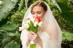 Portrait of beautiful bride smelling bridal bouquet