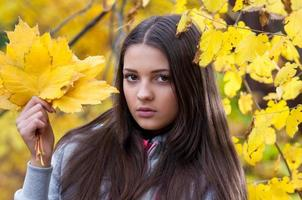 Young girl in a park in autumn photo