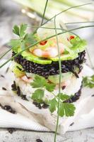 Tower of black and white rice with shrimp and zucchini