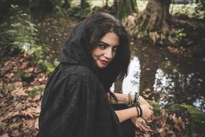beautiful dark vampire woman with black mantle and hood photo