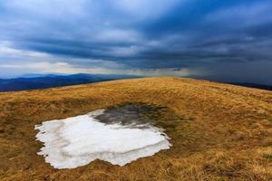 Snow on meadow in Carpathians photo