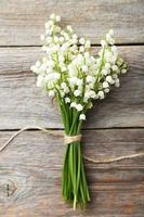 Lily of the Valley on grey wooden background photo