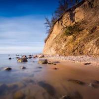 Cliff on sea shore at sunrise. Baltic long exposure photo