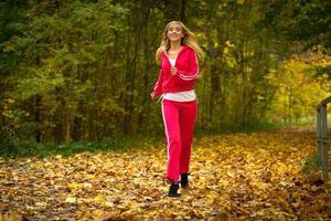 jovem loira correndo correndo no parque outono
