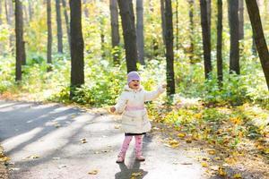 Happy kid girl having fun the autumn park photo