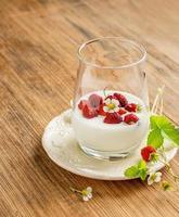 Healthy breakfast cup of fresh milk yoghurt with wild strawberries