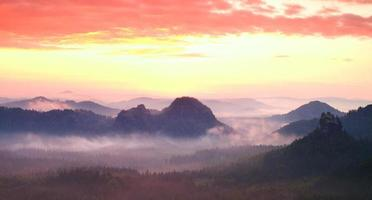 Red misty  landscape panorama in mountains. Fantastic sunrise photo