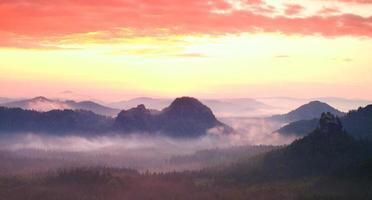 panorama de paisaje brumoso rojo en las montañas. amanecer fantástico
