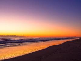 color naranja del amanecer en la larga línea de playa