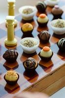 Handmade chocolate candies arranged on the vintage wooden chessbox