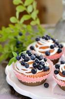 homemade cupcakes with icing and blueberries