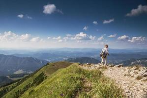 Boy with backpack on mountain hill foot path photo