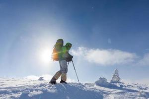 backpacker man wandelen in de winter bergen op zonnige dag