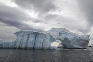 iceberg with arch and gullies on a cloudy autumn day