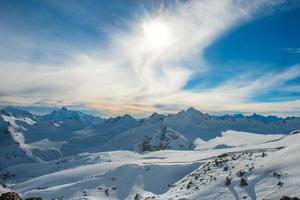 Snowy blue mountains in clouds photo