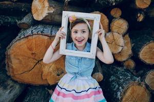 beautiful little girl sitting on trees photo