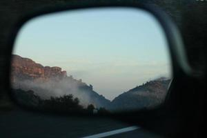 Foggy mountain in rearview mirror