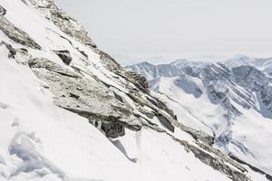Steep mountain slope with frozen rocks photo