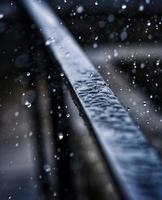 Raindrops falling on railing