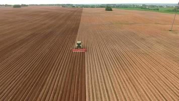 Farmer seeding, sowing crops at field.Aerial view