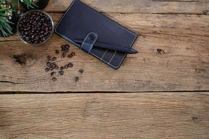 caderno e grãos de café em uma mesa foto