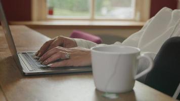 mujer, usar la computadora portátil, en la mesa