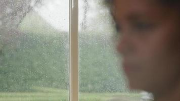 chuva na janela com mulher em primeiro plano video
