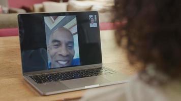 Hombre maduro en la pantalla del portátil durante la reunión en línea