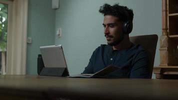 Joven usando audífonos con reunión en línea en casa