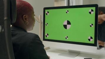 mulher sentada em frente ao monitor do computador com tela verde e ícones