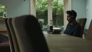 Joven tener reunión en línea en casa usando tableta video
