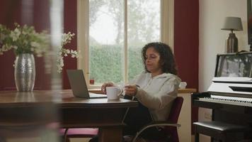 mulher madura usando laptop em casa bebendo chá