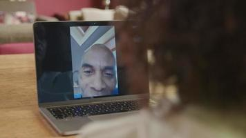 Mature man on laptop screen during online meeting