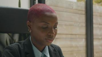 Mujer joven con el pelo rapado trabajando en la oficina en casa
