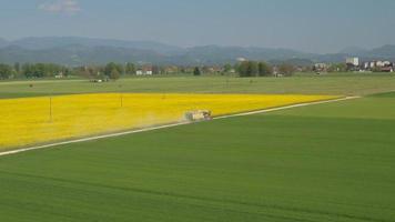 Antena: agricultor conduciendo un tractor con remolque en una carretera polvorienta por campo de colza