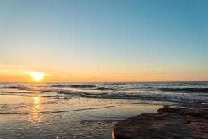 Ocean beach at the sunset photo