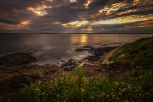 puesta de sol en una orilla rocosa.