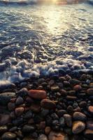 Olas en la playa en marea alta de piedras redondas foto