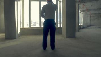 uomo d'affari, agente immobiliare, investitore in elmetto che cammina in un edificio non finito. grattacielo all'interno in costruzione