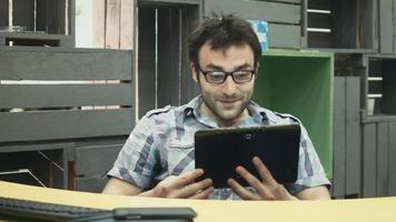 homme parlant sur tablette au lieu de travail