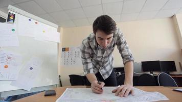 l'architetto copia la bozza dal layout originale utilizzando carta carbone