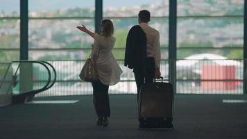 socios comerciales caminando hacia la escalera mecánica del aeropuerto, llevando equipaje, turismo video