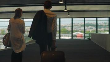 pareja en ropa formal caminando en el aeropuerto con bolsas, viaje de negocios, socios video