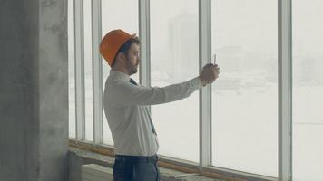 maestro constructor, empresario con casco dentro de un sitio de construcción inspeccionando el progreso de la construcción con tableta. disparar deslizador video
