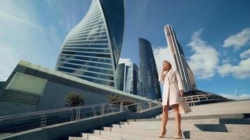 Hermosa joven mujer de negocios llamando por teléfono en el fondo de los rascacielos