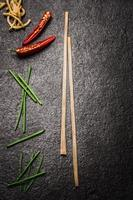 Dark asian food background with chopstick, chili and noodles