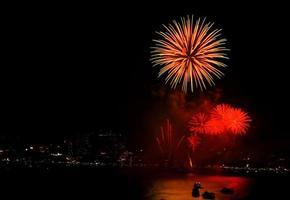 Fuegos artificiales sobre la ciudad de noche con reflejo en el agua