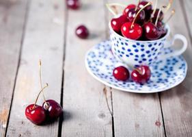 Fresh cherry in a blue ceramic cup photo